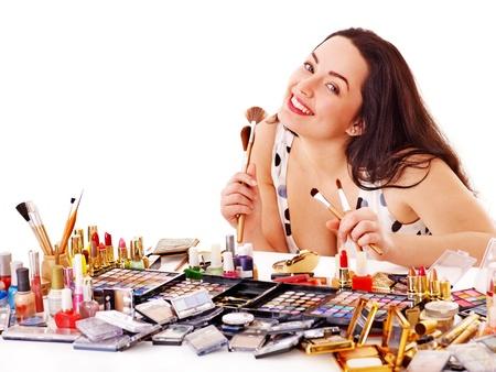 Happy young woman applying makeup. Isolated. photo