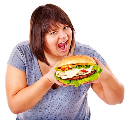high calorie foods: Happy overweight woman eating hamburger. Isolated. Stock Photo