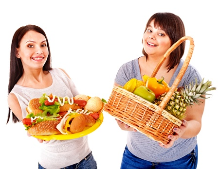 chubby woman: Thin and big women choosing between fruit and hamburger. Stock Photo