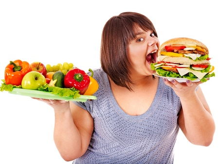 junkfood: Woman choosing between fruit and hamburger. Isolated.