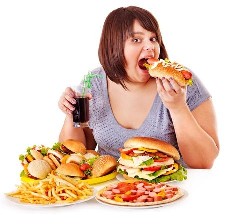 sobre peso: Mujer con sobrepeso come comida rápida. Foto de archivo