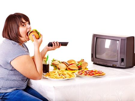 Big woman eating fast food and watching TV. Isolated. photo