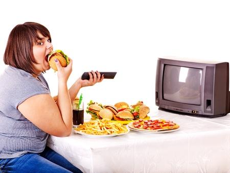 ver tv: Gran mujer comiendo comida rápida y viendo la televisión. Aislado. Foto de archivo