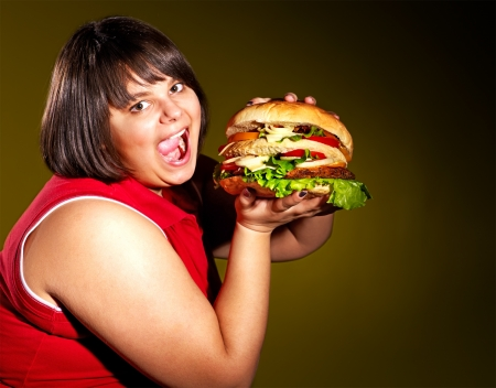 beefburger: Overweight woman eating hamburger.
