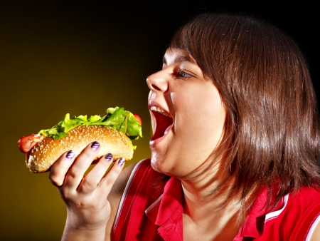 high calorie foods: Overweight hungry woman eating hamburger.