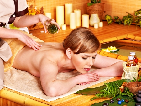 Woman getting stone massage in  spa near water. photo