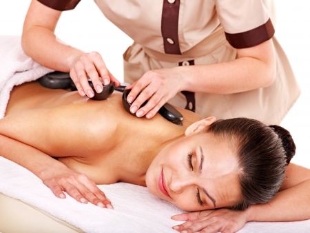 hot stone massage: Woman getting stone therapy massage. Isolated on white. Stock Photo
