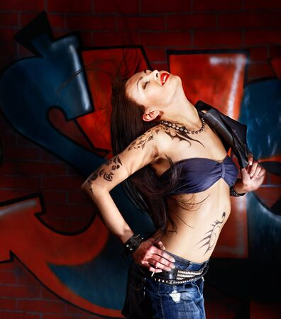 body art: Beauty woman with body art aganist graffiti brick wall. Stock Photo