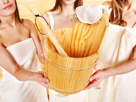 Sauna bucket  holding by group woman. Concept. photo