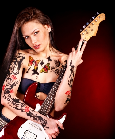 woman guitar: Young woman with tattoo playing guitar. Stock Photo