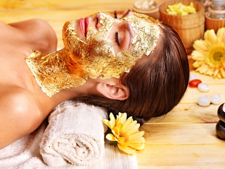 gold leaf: Woman getting  gold facial mask.