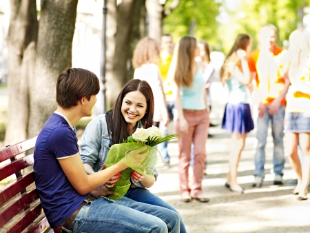 Couple of teenager on date outdoor. Group of people in background. photo