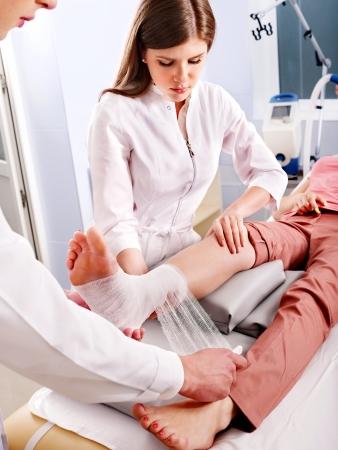 Doctor bandaging foot patient in hospital.
