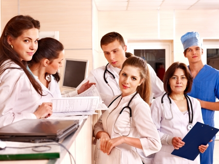 standing reception: Group doctors and patient standing at reception in hospital. Stock Photo
