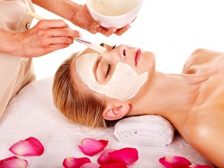 gezichtsbehandeling: Vrouw met klei gezichtsmasker met roze bloemblaadje. Geïsoleerd.