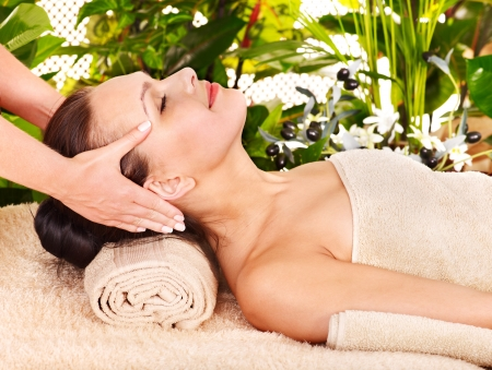 head massage: Woman getting facial massage in tropical beauty spa. Stock Photo