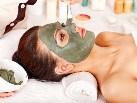 spa mud: Woman with clay facial mask in beauty spa. Stock Photo