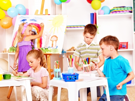 nursery education: Group child painting at easel in school.