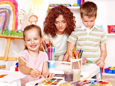 art activity: Child with teacher painting  in start school. Stock Photo