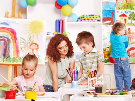 children painting: Children with teacher painting at easel in school.