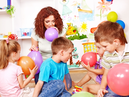 nursery education: Child with teacher inflating balloons in school. Stock Photo