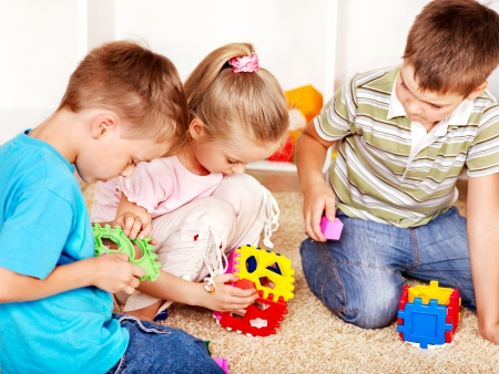 nursery school: Children in kindergarten stacking block.