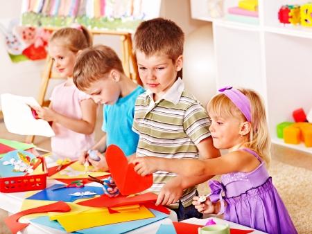 Child boy cutting out scissors paper in preschool.