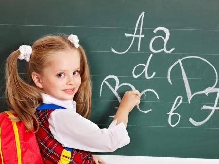 schoolroom: Schoolchild writting on blackboard in schoolroom. Stock Photo