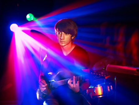 Man playing  guitar in night club. Lighting effects. photo