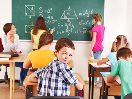 classroom: School child with teacher in classroom. Stock Photo