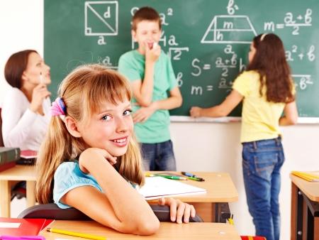 classmates: School child with teacher in classroom. Stock Photo