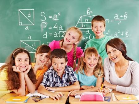 Dzieci: Dziecko w szkole z nauczycielem w klasie. Zdjęcie Seryjne