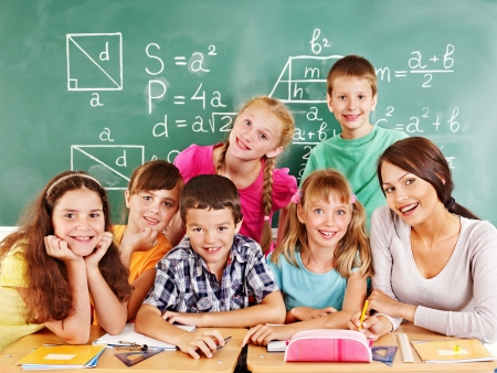 classmate: School child with teacher in classroom. Stock Photo