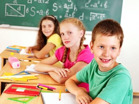 classmates: Teen school child sitting on desk in classroom.