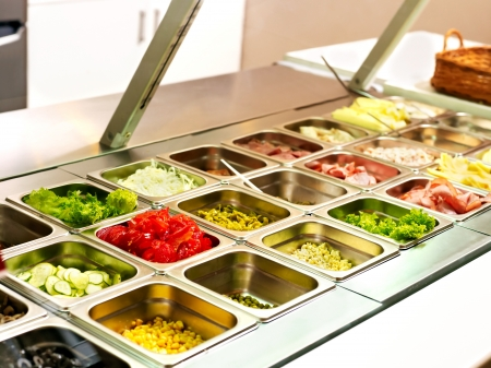 cafeterias: Tray with cooked food on showcase at cafeteria. Stock Photo