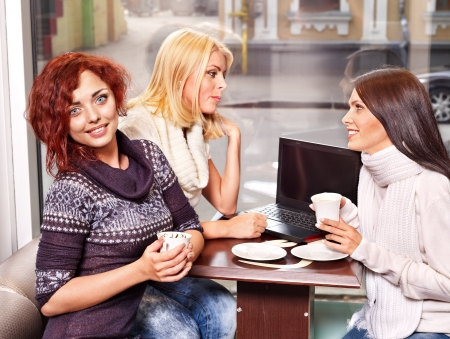 winter break: Three young women at laptop drinking coffee in a cafe. Stock Photo