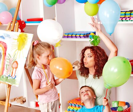 Child with teacher inflating balloons in school. photo