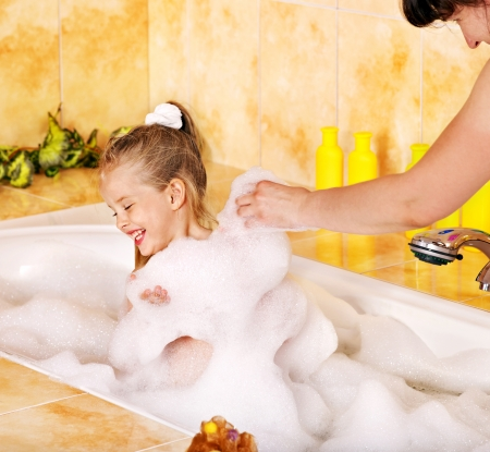 Mother and happy child washing in bubble bath . photo