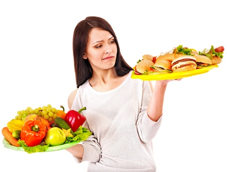 Thinking woman choosing between fruit and hamburger. photo