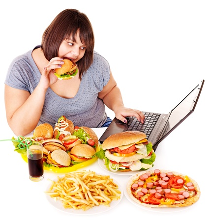 take out food: Woman eating fast food at working pc. Isolated.