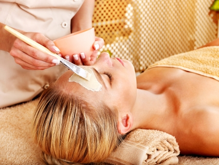masajes faciales: Mujer blanca recibiendo máscara facial en el spa de belleza tropical. Foto de archivo