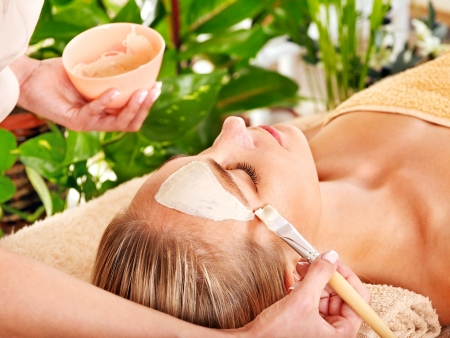 body mask: Woman getting facial mask in tropical beauty spa. Stock Photo