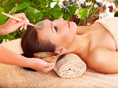 tratamiento facial: Mujer con m�scara facial de barro en el spa de belleza. Foto de archivo