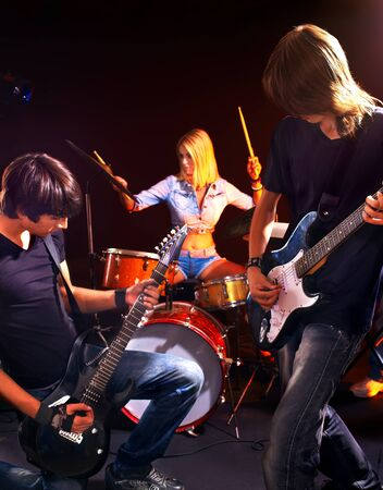 cymbals: Group peole playing  guitar in night club.