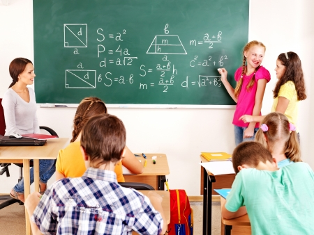 girls back to back: School child with teacher in classroom. Stock Photo