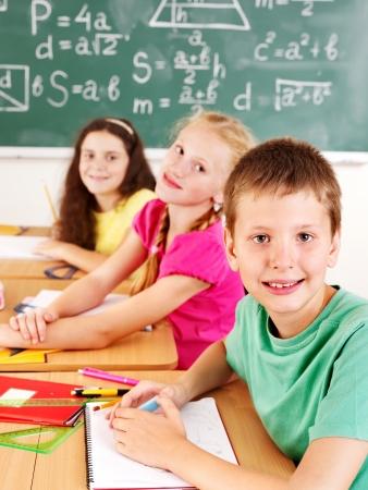 school teens: Group of school child sitting on desk in classroom.