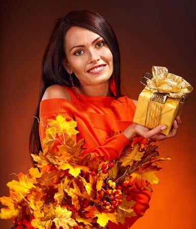 Woman holding gold gift box . Autumn season. Stock Photo - 15300388
