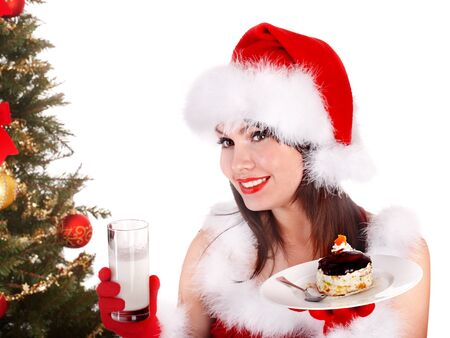 Christmas girl in red santa hat and cake on plate. Isolated. photo