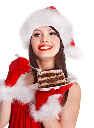 woman eating cake: Christmas girl in red santa hat eating cake on plate. Isolated.