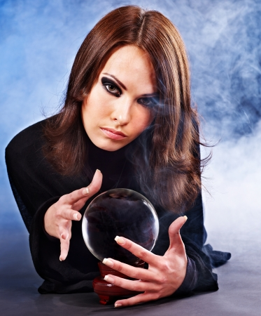 Young woman with crystal ball. Fortune telling. photo